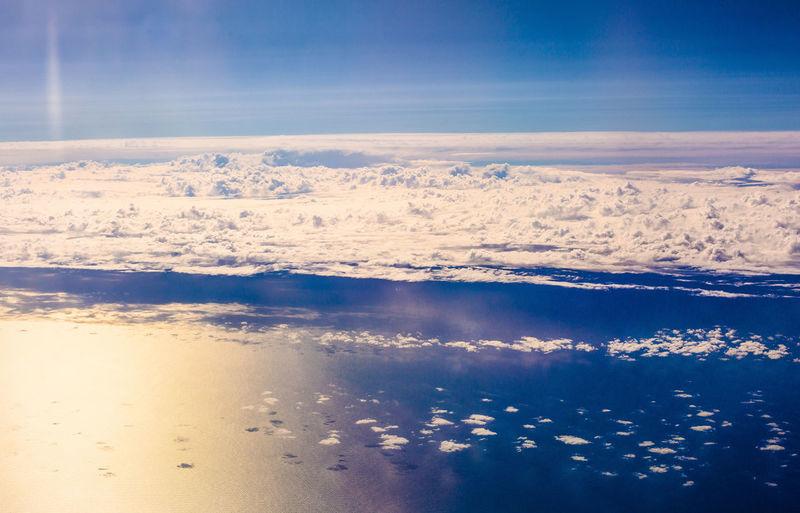 Clouds hovering above the vast reflective ocean waters below - queenstown, new zealand