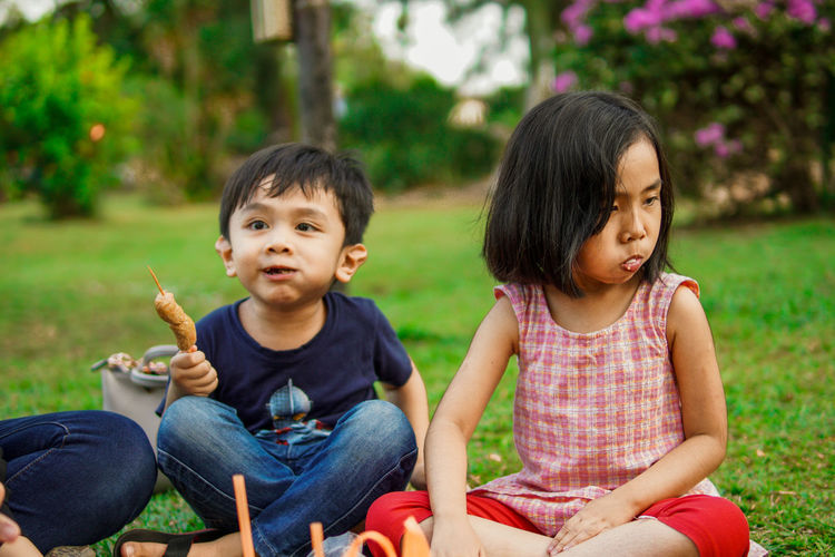 Naughty kids on picnic blanket together in park, playing with food