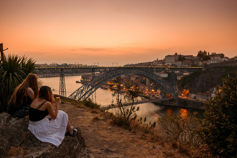 Rear view of women looking at bridge over river against orange sky during sunset