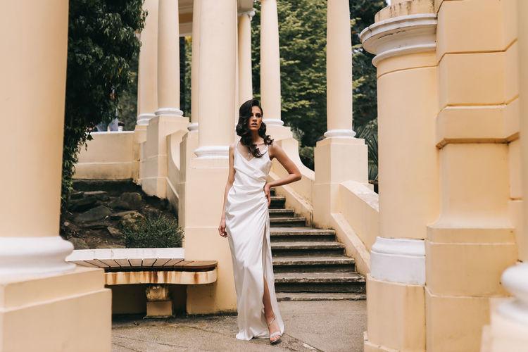 A beautiful brunette lady in an elegant wedding dress poses among the columns in the old city park