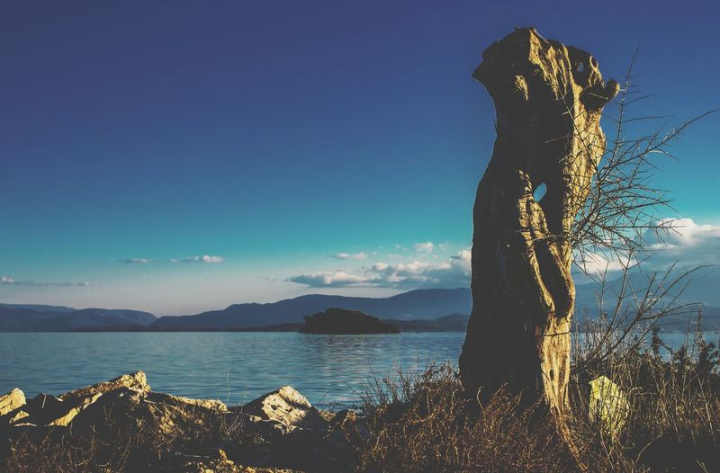 Scenic view of rocks against blue sky