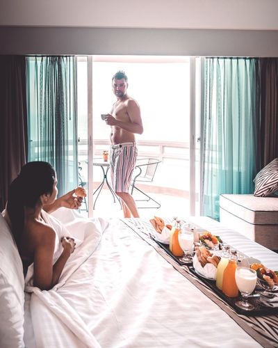Shirtless man looking at woman on bed at hotel