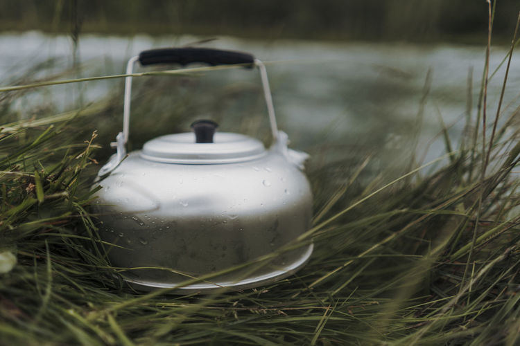 Close-up of tea light on field by water