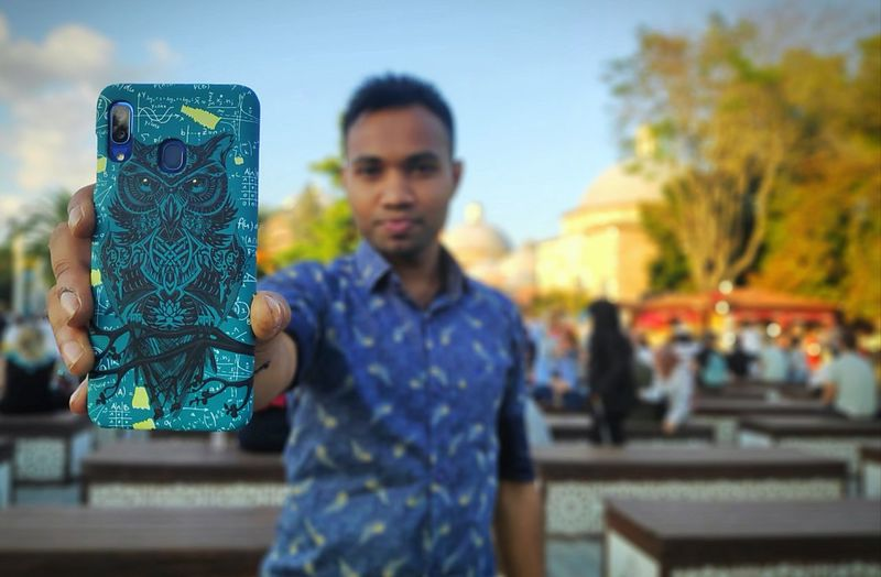 Young man using smart phone while standing outdoors