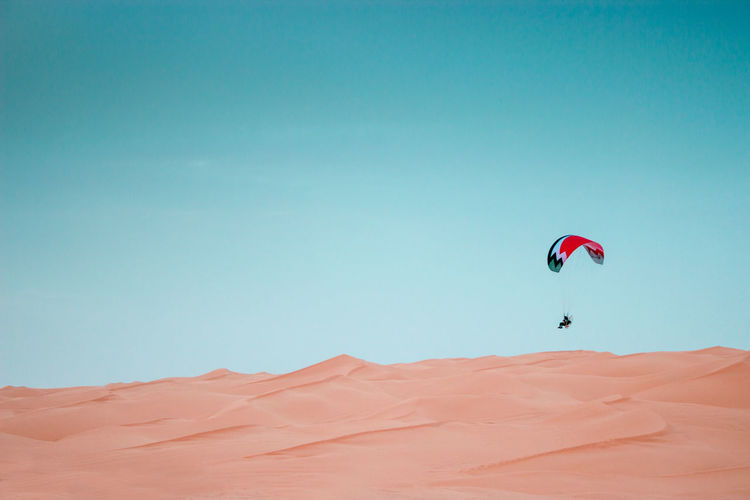 Paramotor, Sahara Desert Adventure Extreme Sports Parachute Sky Sport Scenics - Nature Paragliding Real People Blue Unrecognizable Person Copy Space Desert Leisure Activity Nature Mid-air One Person Land Clear Sky Flying Day Arid Climate Climate Sahara Paramotor Tunisia 2018 In One Photograph