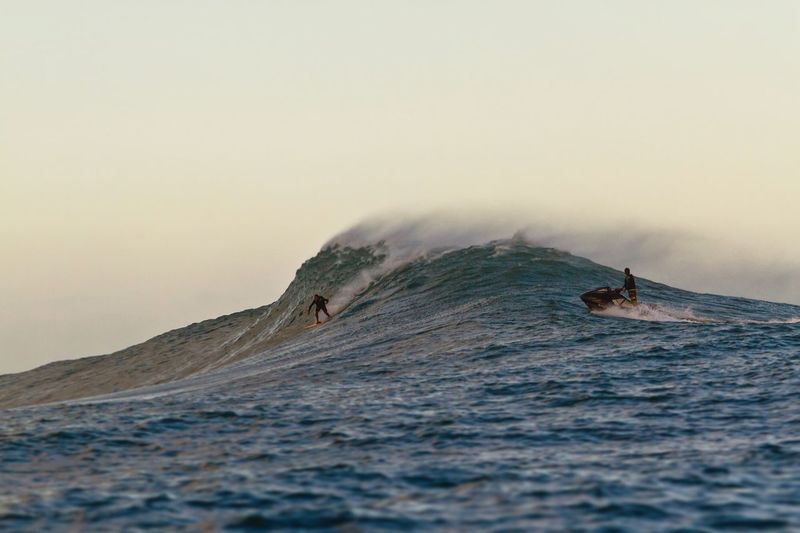 Big wave tow in surfers