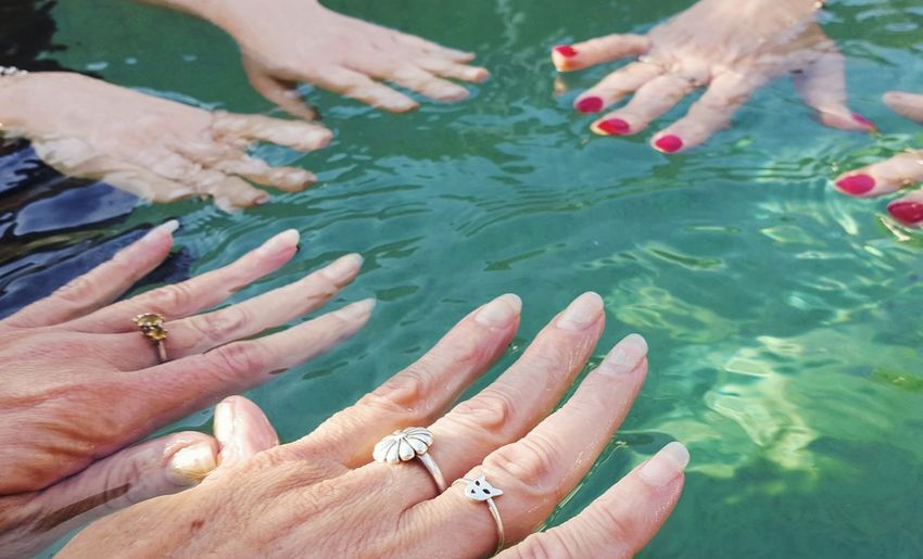 Cropped hands of woman in swimming pool