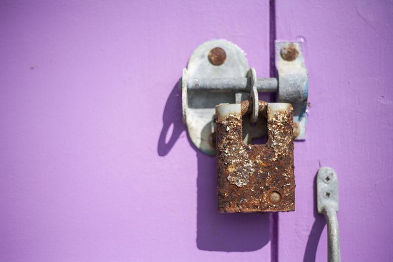 Close-Up Of Rusty Padlock On Purple Door