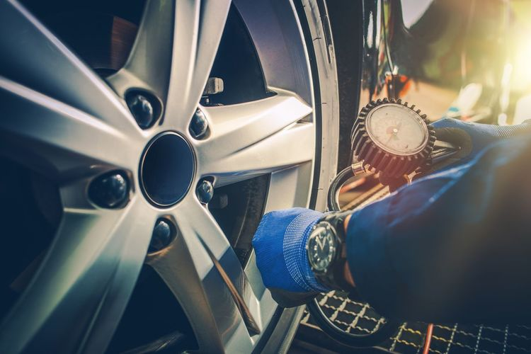 Cropped image of mechanic hand checking tire pressure in garage
