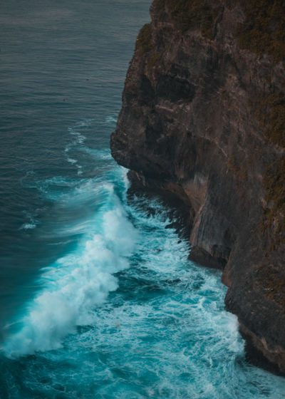 High angle view of sea waves splashing against rock formation