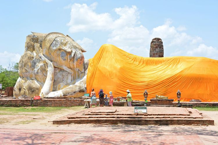 People by reclining buddha statue at wat phra ram