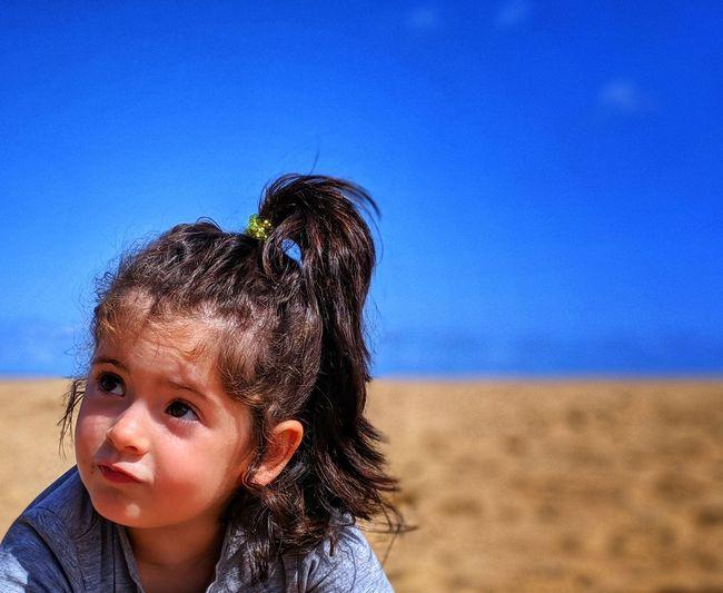 Cute girl at beach against blue sky