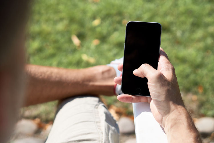 Cropped image of man using blank phone while sitting outdoors