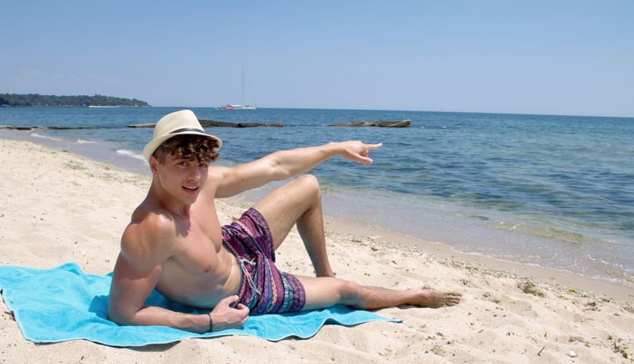 Portrait of shirtless man pointing while relaxing at beach against clear sky
