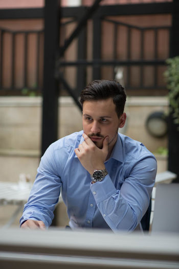 Thoughtful businessman sitting on table outdoors