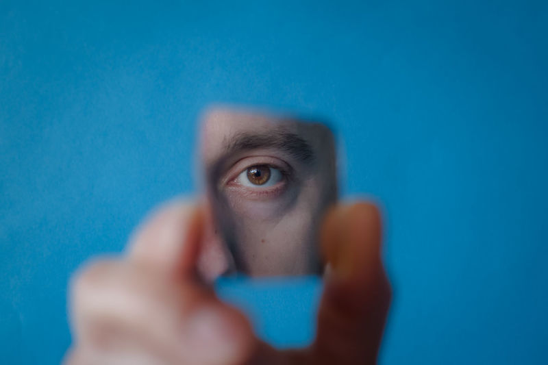 Portrait of human hand holding blue eyes