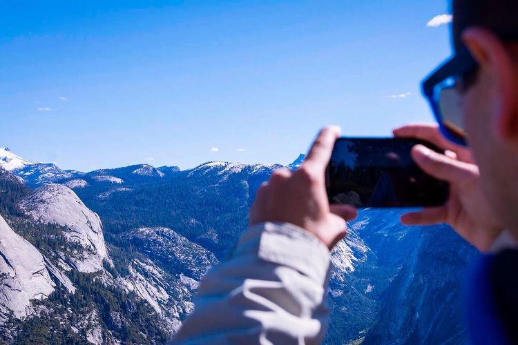 Cropped Image Of Man Photographing Snowcapped Mountains Using Phone Against Sky