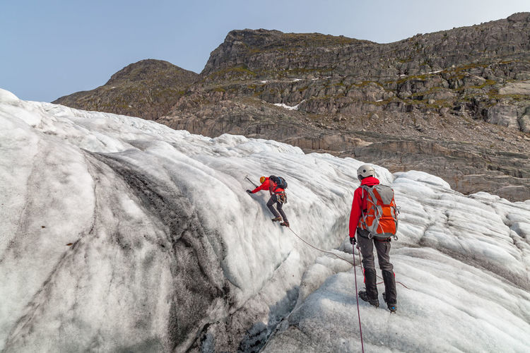 People hiking on snow covered mountains at jostedalsbreen