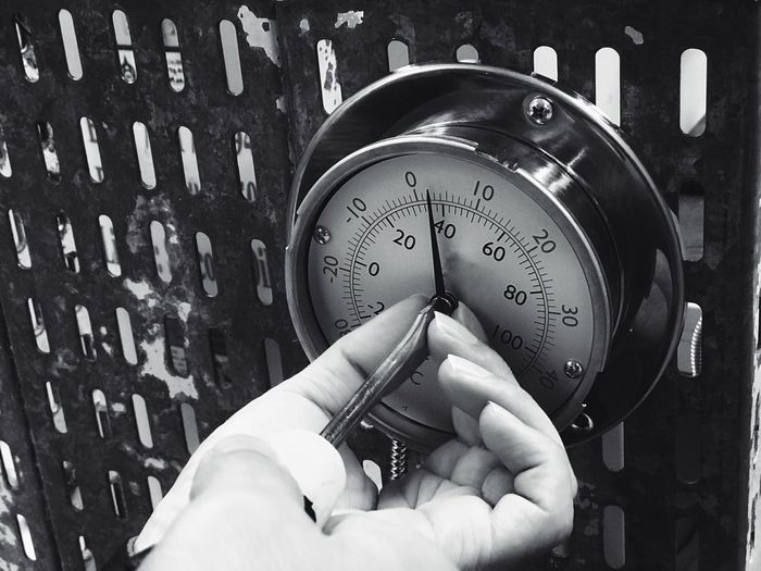 Close-up of hands touching gauge