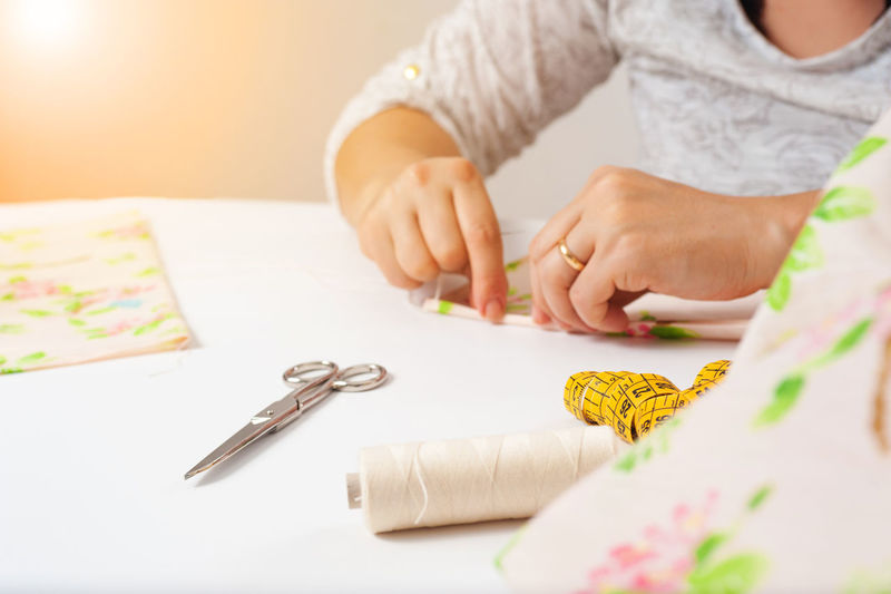 Midsection of women sewing at home