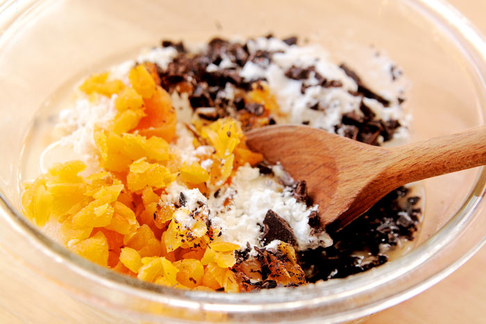 Mixing dried apricots into flour with chopped chocolate pieces Dark Chocolate Homemade Food Natural Light Textures Wooden Spoons Baking Batter Close-up Day Dried Apricots Flour Food Prep Home Cooking Indoors  Mixing Bowl No People Studio Shot Wooden Spoon