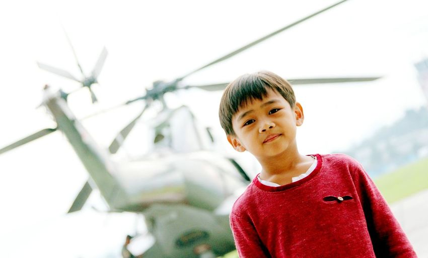 Close-Up Of Boy Standing Against Helicopter