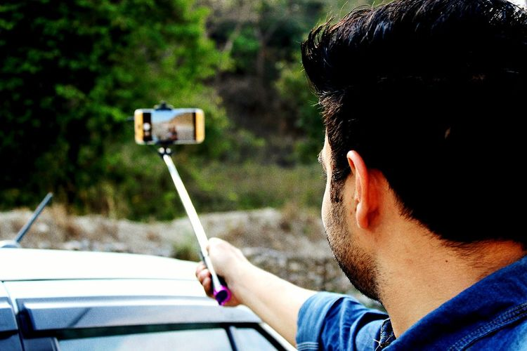 Man holding monopod while taking selfie from mobile phone by car