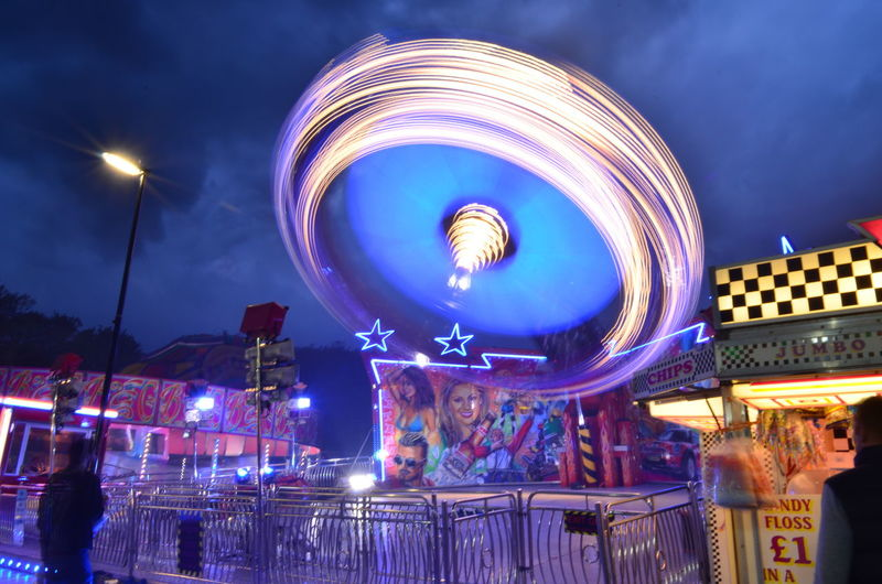 Amusement Park Amusement Park Ride Architecture Arts Culture And Entertainment Blurred Motion Building Exterior Built Structure Carousel City Cloud - Sky Ferris Wheel Illuminated Incidental People Leisure Activity Long Exposure Motion Nature Night Nightlife Outdoors Sky Spinning