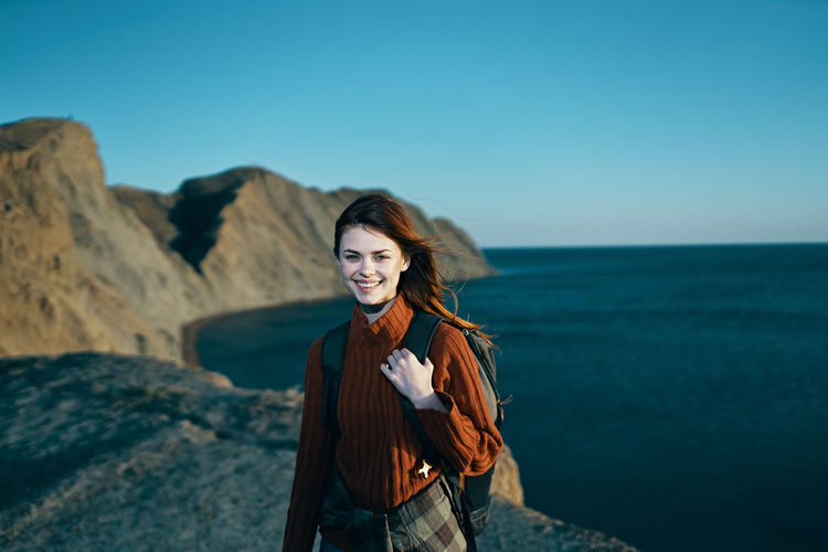 Young woman standing at sea shore against sky