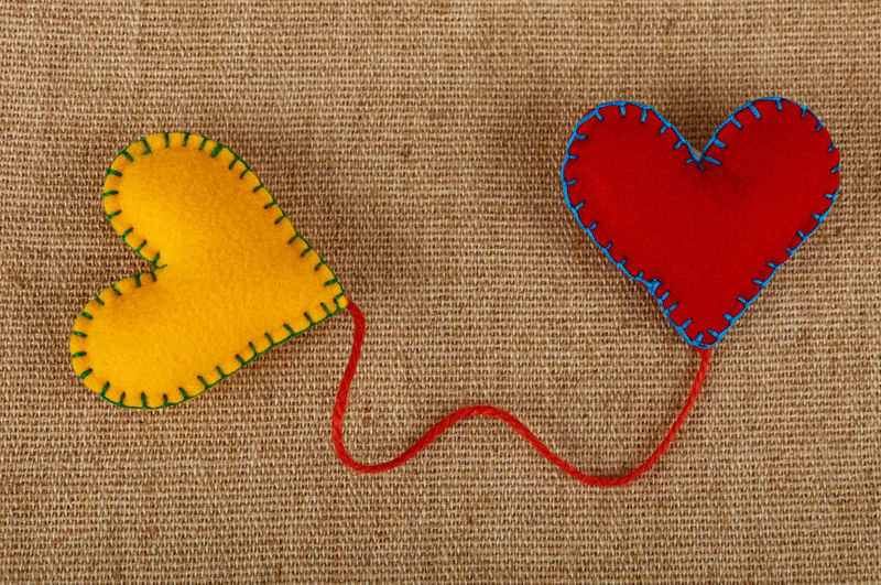 Two felt craft handmade stitched hearts, red and yellow, connected together with twine thread over canvas background Canvas Close-up Connected Couple Craft Design Felt Heart Heart Shape Heart To Heart  Link Love Paint The Town Yellow Red Romance Romantic Shape Stitched Togetherness Two Two Hearts Valentine Valentine Card Valentine's Day  Valentine's Day - Holiday