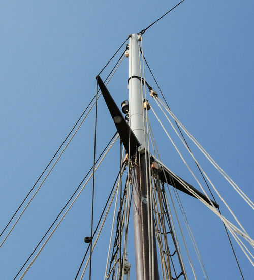 Low angle view of ship against clear blue sky
