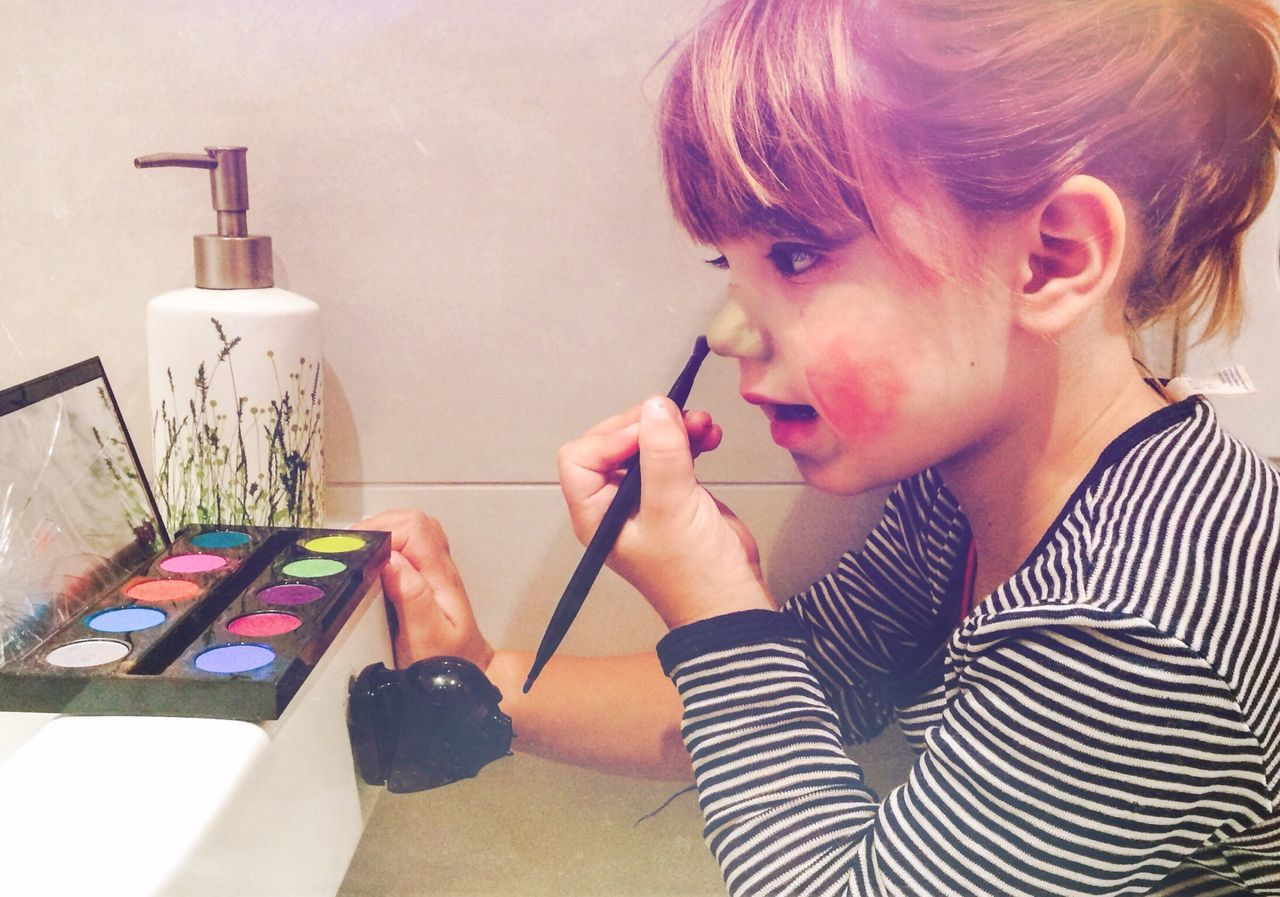 Side view of cute girl applying make-up at home