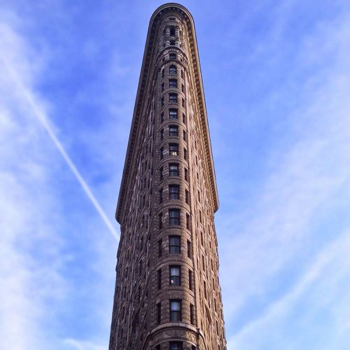 Low angle view of flatiron building against blue sky