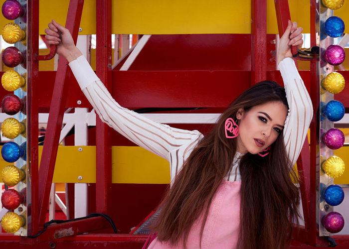 Portrait Of Female Model Standing Amidst Colorful Light Bulbs At Amusement Park
