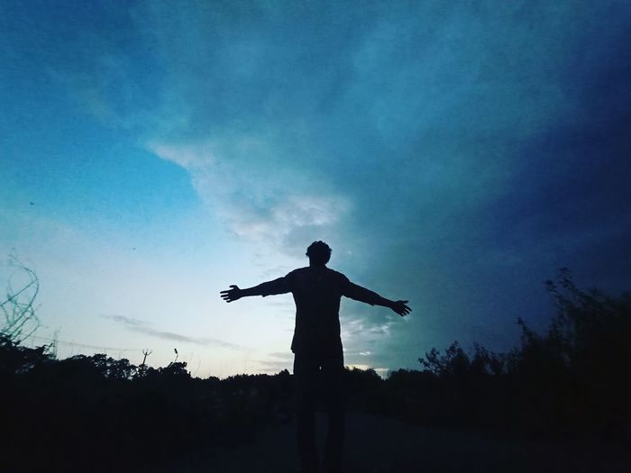 Silhouette man with arms outstretched standing against sky