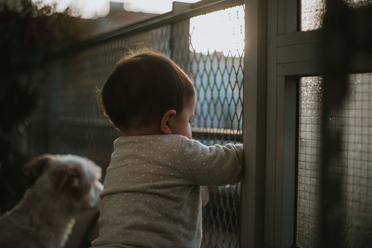 Child And Dog Pets Pet Child Childhood Real People One Animal One Person Window Lifestyles Leisure Activity Looking Domestic Mammal Innocence Outdoors Rear View Togetherness Together Friendship Home Family Family With One Child Family Matters Spring Spring Has Arrived