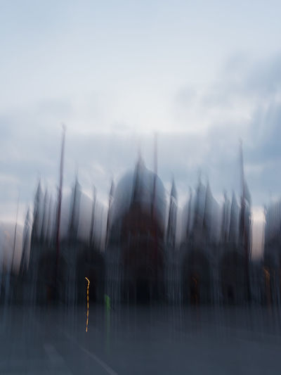 Blurred motion of cars on road by buildings against sky
