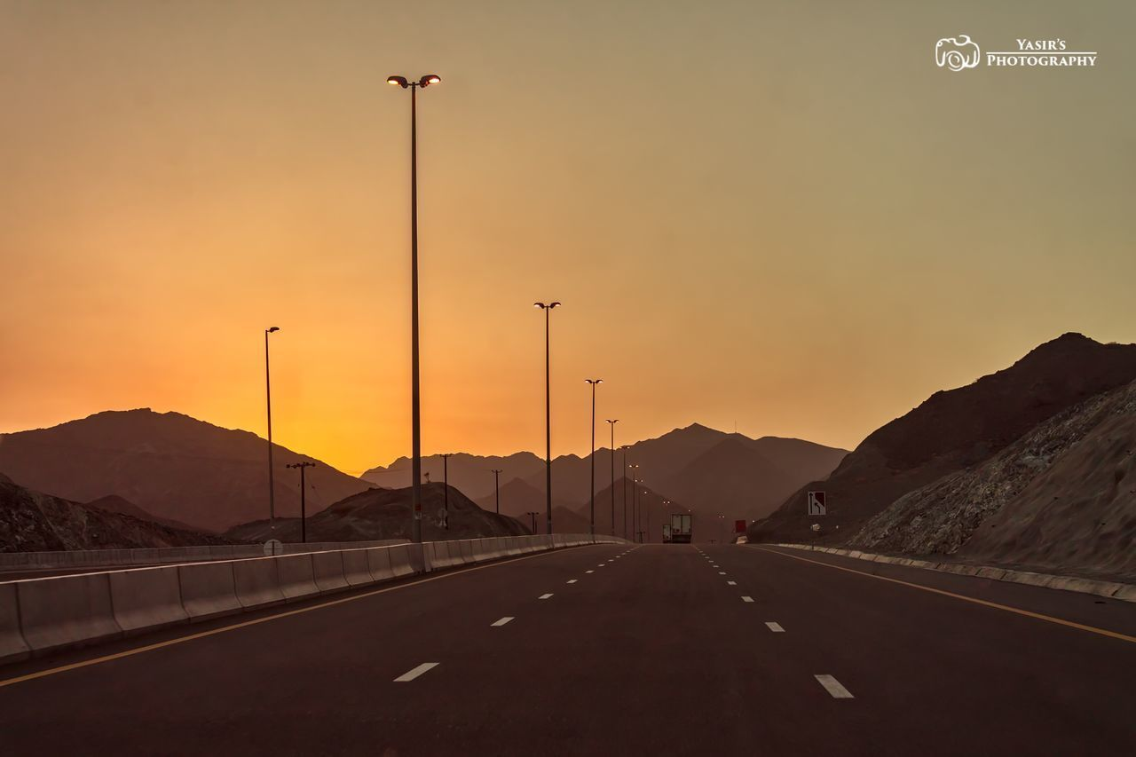 transportation, road, mountain, the way forward, car, road marking, sunset, highway, beauty in nature, nature, mountain range, land vehicle, scenics, street light, mode of transport, no people, outdoors, road sign, road trip, landscape, illuminated, sky, day