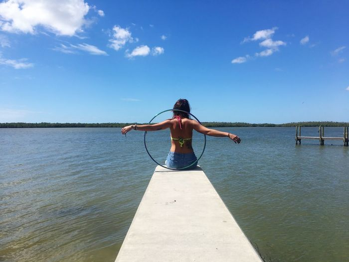 Rear view of young woman with plastic hoop sitting on pier over lake against sky during sunny day