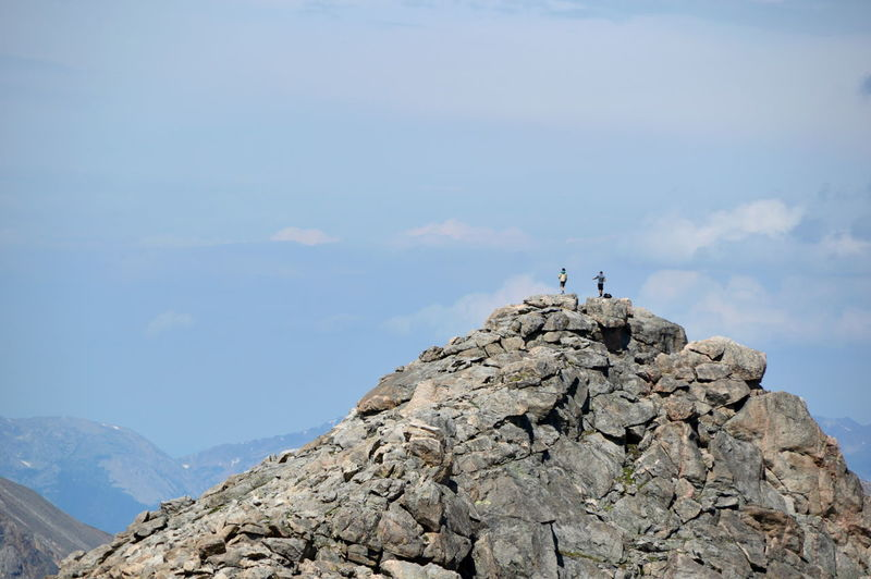 Low angle view of people standing on rocky mountains against sky