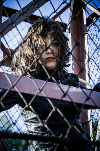 Low Angle Portrait Of Woman Trapped In Metallic Cage