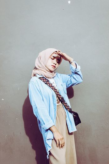 Woman in hijab shielding eyes while standing against wall