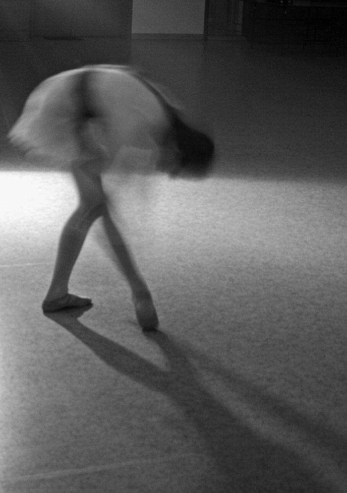 Blurred motion of ballet dancer dancing in studio