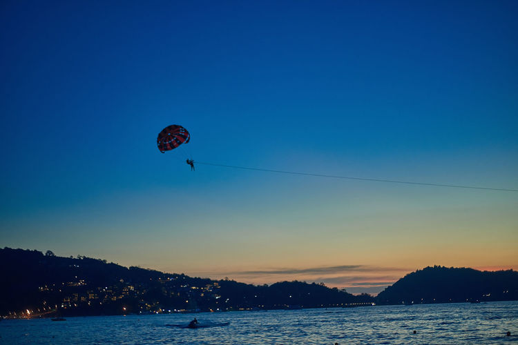 Low Angle View Of Person Parasailing Over River Against Sky At Dusk