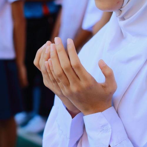 Midsection Of Schoolgirl Standing In Prayer Position