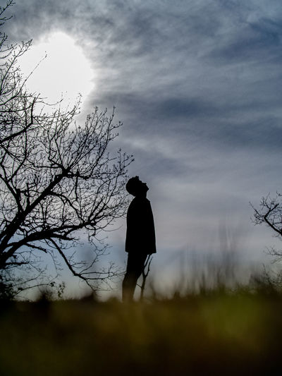 Silhouette man standing on field against sky