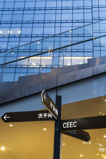 Low angle view of sign on glass building