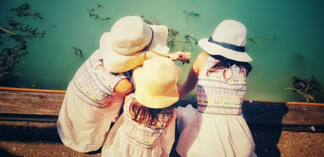 High angle view of girls wearing hat crouching on pier over lake