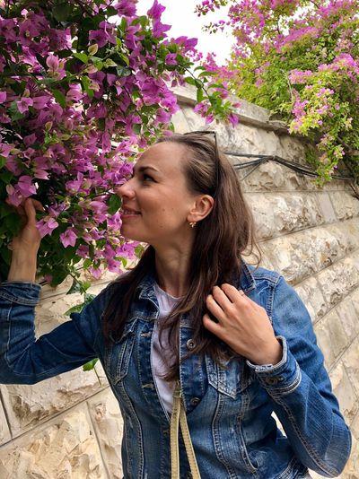 Smiling Woman In Denim Jacket Touching Flowering Plant