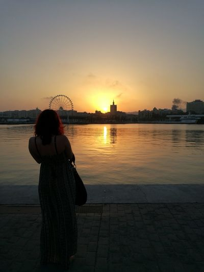 Woman Watching Sunset And Modern City By Bay